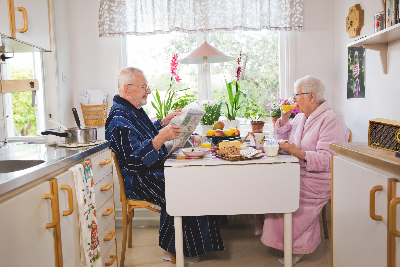 Schwedisches älteres Paar am Frühstückstisch hört Radio